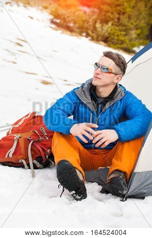 A Man Sits In A Tent In The Winter.