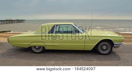 FELIXSTOWE, SUFFOLK, ENGLAND - AUGUST 27, 2016: Classic Yellow Thunderbird motor car  parked on seafront promenade.