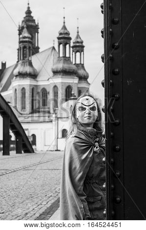 Teen girl in superhero costume. Bridge and the Catholic Cathedral in the background. Black and white noir photo.