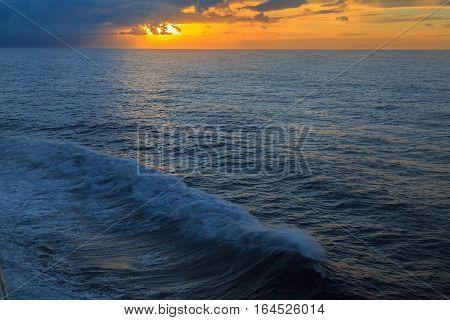 Sunset over atlantic ocean with ocean waves.