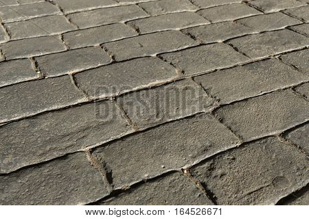 Gray stamped concrete pavement outdoor, mimics cobblestones pattern, decorative appearance colors and textures of paving cobble stone, perspective flooring exterior
