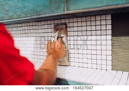 Industrial Worker Leveling Mosaic Ceramic Pattern Tiles On Bathroom Shower Area