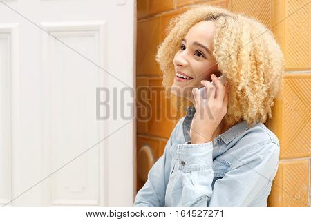 Cheerful girl talking on a cell phone. Young smiling girl talking on the phone