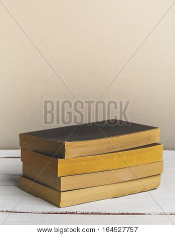 Vintage novel paperback books on wooden table. Copy space. Vertical image
