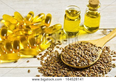 Brown flax seeds on spoon and flaxseed oil in glass jug on wooden table. Flax oil is rich in omega-3 fatty acid.