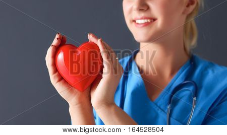 Young doctor woman with stethoscope holding heart .