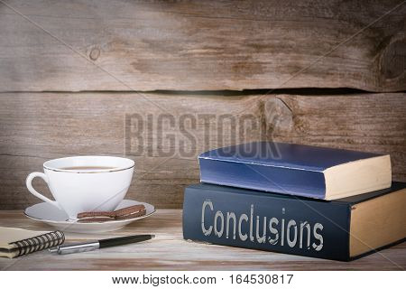 Conclusions. Stack of books on wooden desk.