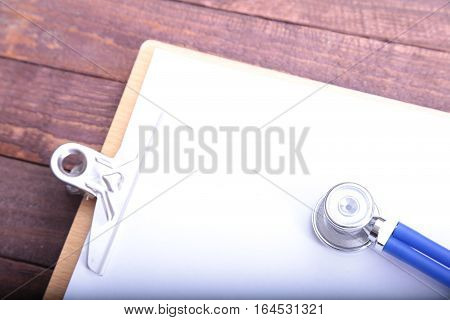 Closeup of a medical stethoscope with folder on wooden background.