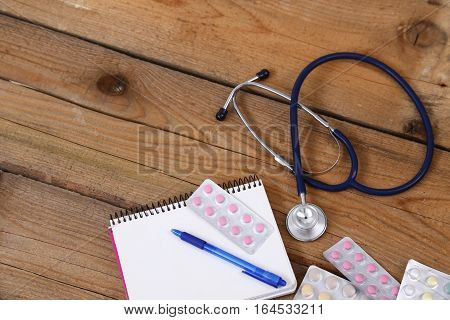 Stethoscope and tablets isolated on wooden background.