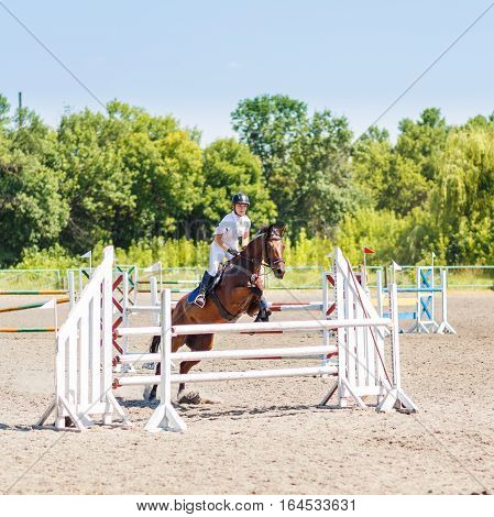 Young rider girl in white shirt on bay horse jumping over hurdle on show jumping competition