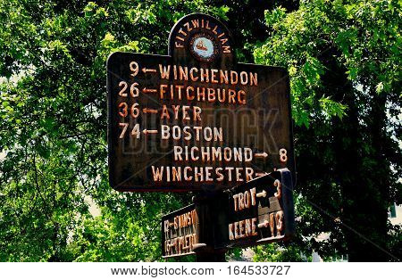 Fitzwilliam,New Hampshire - July 11, 2013:  Rusting iron sign post on the Village Green shows distances between various owns and cities from Fitzwilliam
