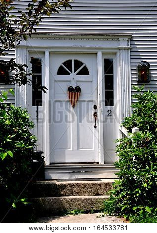 Fitzwilliam New Hampshire - July 11 2013: Handsome 18th century colonial doorway with early American flag wooden knocker and fan window