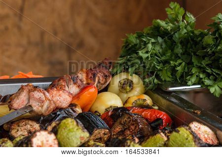 Pan with grilled vegetables, pepper, eggplants, zucchini, grilled meat, parsley on background. Food festival on open air