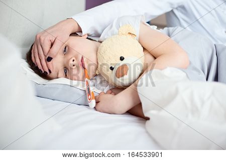Sick Little Child With Temperature In Bed.