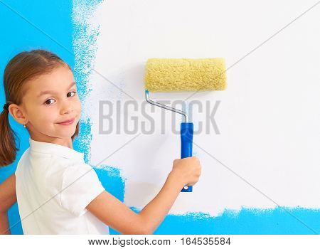 7 years old girl painting the wall in her room, close up