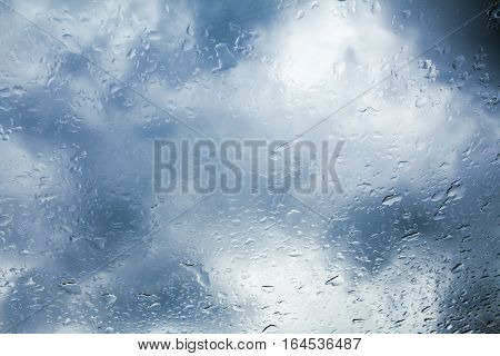 Wet window with background of dark cloudy sky.