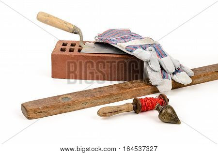 Old construction accessories trowel bricks plummet and level on white background.