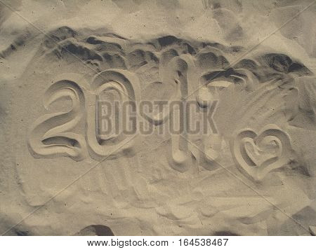 2017 written on a sandy beach in the afternoon