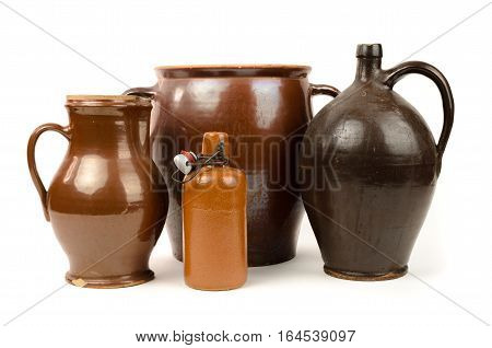 Old stoneware bottles and clay jug isolated on white background