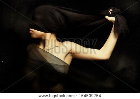 Artistic portrait. Woman blinded by a cloth hiding face. Rebellion and silence. A young woman is blinded by a cloth pulled from hand. artistic portrait with grunge background. A silk veil covering her breasts.