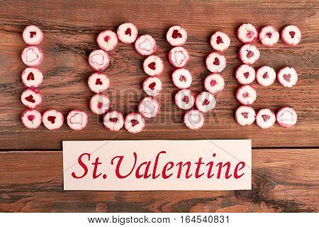 Saint Valentine's Day greeting card. Candies on wooden background. Be my Valentine.