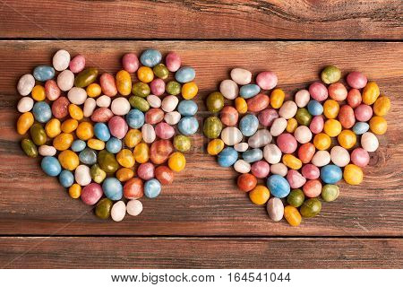 Colorful candy hearts on wood. Heart-shaped candy pebble piles. Confectionery as art.