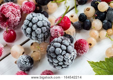 frozen berries: black currant red currant white currant and currant leaves top view macro.
