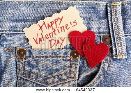 Red hearts on jeans pocket. Greeting paper on Valentine's Day. Be romantic and creative.