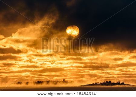 Sun appear through dark clouds above Baltic Sea that is about to freeze over with islands in horizon and sea smoke rising from the sea water.