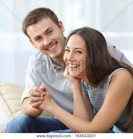 Happy couple posing and looking at you with the girlfriend in foreground sitting on a sofa in the living room at home