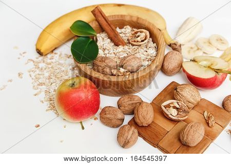 There are Banana,Apple,Walnuts in the Wooden Plate and Rolled Oats,Wooden Spoon,Trivet,with Green Leaves,Healthy Fresh Organic Food on the White Background