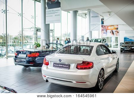ROME ITALY - MARCH 10 2014: Agents selling BMW cars inside car dealer showroom. The BMW Group recorded increasing of sales in Italy.