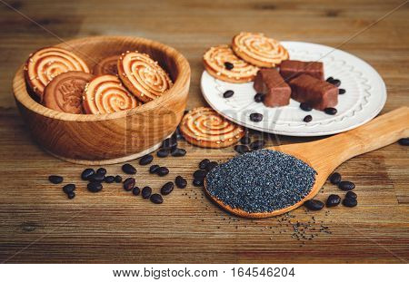 There are Cookies,Candy,Chocolate Peas,Poppy;China Saucer,Tasty Sweet Food on the Wooden Background