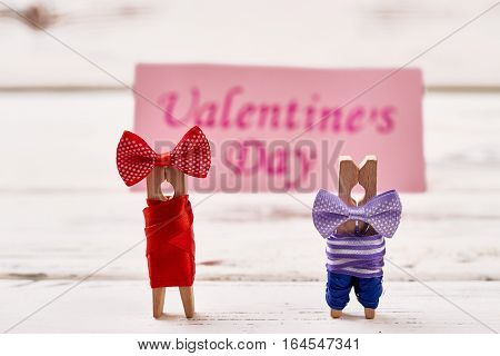 Clothespin couple on wooden background. Greeting card and clothespin couple. Prepare surprise on Valentine's Day.