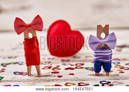Clothespin couple on heart backdrop. Red heart and dressed pegs. Small gesture of big love.