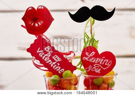 Loving you card and candies. Prop mustache, lips on wood. How to create romantic atmosphere.