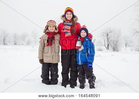 Three kids standing together on white snow, outdoors winter vacation