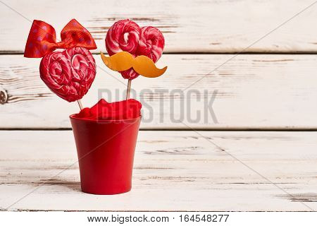 Red flowerpot with heart-shaped lollipops. Candies with bow and mustache. Recipe of handmade sweet gift.