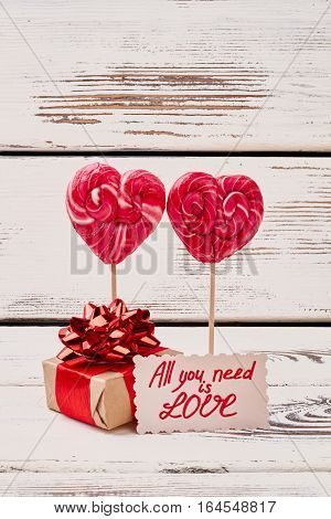 Present box and lollipops. Love inscription on card. Never stop surprising your beloved.