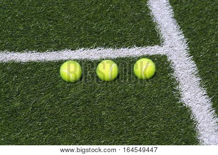 Three yellow tennis balls lays in-line on green synthetic court grass marked with white lines