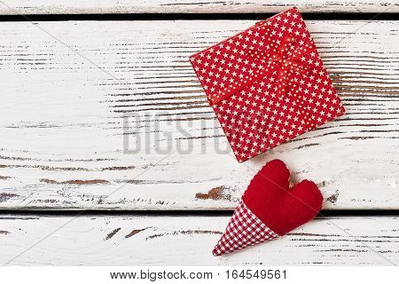 Fabric heart near gift box. Present wrap with star pattern. Interesting idea for greeting.