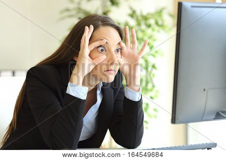 Sleepy businesswoman trying to stay awake keeping the eyes opened with the fingers watching a desktop computer monitor at office poster