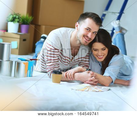 Couple choosing paint color from swatches for new home lying on wooden floor.
