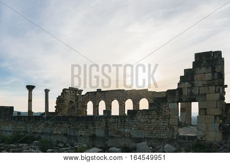 The exterior of the Basilica at Volubilis on a sunny day with few clouds and blue sky, Morocco.