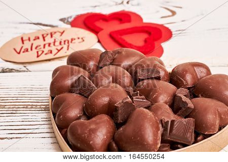 Heart-shaped chocolates in box. Card, red hearts and candies. Love is the answer.