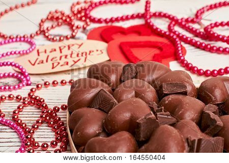 Bead garland and sweets. Candies in box near hearts. Make your beloved happy.