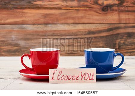 I Love You card. Cups near greeting paper. Nice morning tradition.