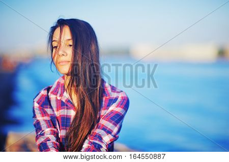 Young attractive brunette girl in red-and-blue plaid shirt shredded by the wind long hair with a wistful glance in the sunset on blurred background blue waters of river.