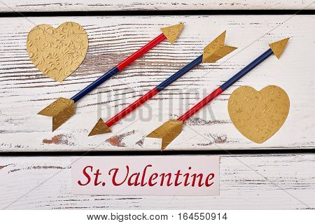 Golden hearts near arrows. Valentine's Day card near arrows. Believe in fairy tale.