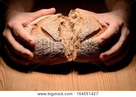 Breaking bread on a wooden table dark background